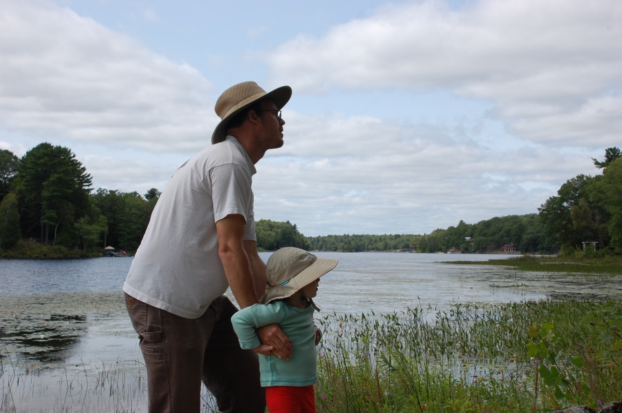Photograph of Jay holding daughter Iris on shore of Horseshoe Lake, Ontario.